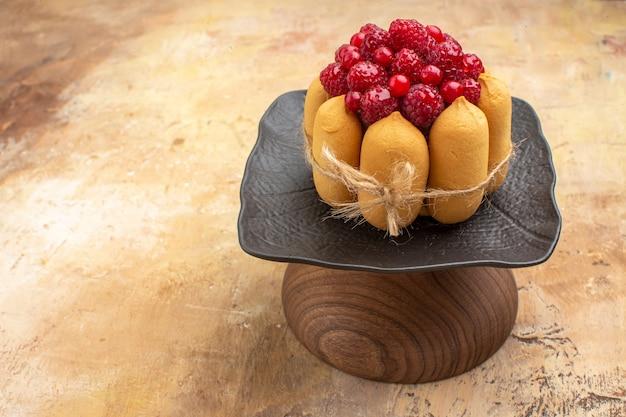 Zijaanzicht van gedekte tafel voor koffie en theetijd met frambozen op taarten op gemengde kleurentafel