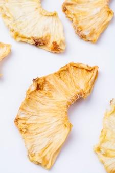 Zijaanzicht van gedroogde ananas segmenten geïsoleerd op een witte achtergrond
