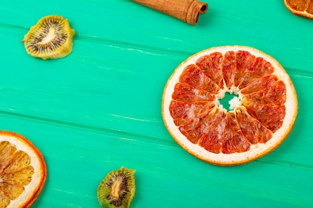 Zijaanzicht van gedroogde grapefruit en stukjes sinaasappel met kaneelstokjes en gedroogde kiwiplakken op groene houten achtergrond