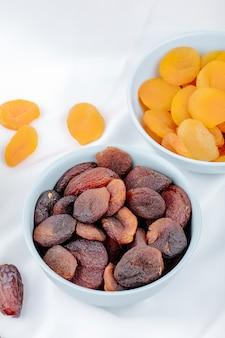 Zijaanzicht van gedroogde vruchten abrikozen en gedroogde datums in kommen op wit tafellaken op houten achtergrond