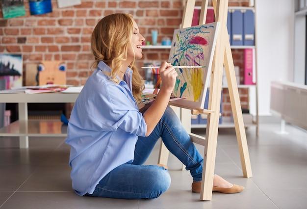 Zijaanzicht van gefascineerde vrouwelijke artiest