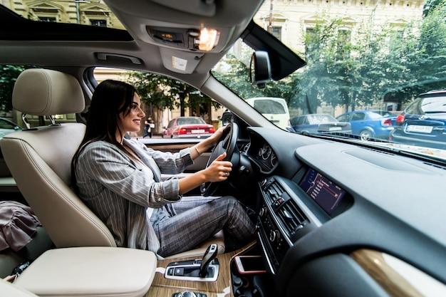 Zijaanzicht van gefrustreerde jonge bedrijfsvrouw die een auto drijft.