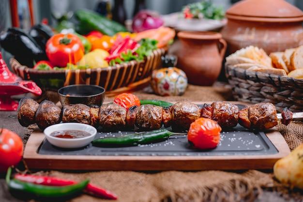 Zijaanzicht van gegrilde aardappelen op shish geserveerd met groenten en sauzen op een houten bord
