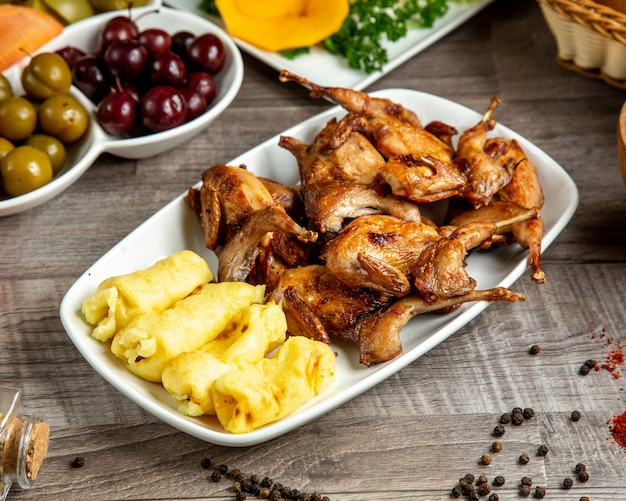 Zijaanzicht van gegrilde kwartel met lula kebab van aardappelen geserveerd met augurken op tafel