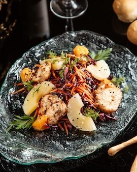 Zijaanzicht van gehakte groente salade met kip en ananas op een plaat op tafel