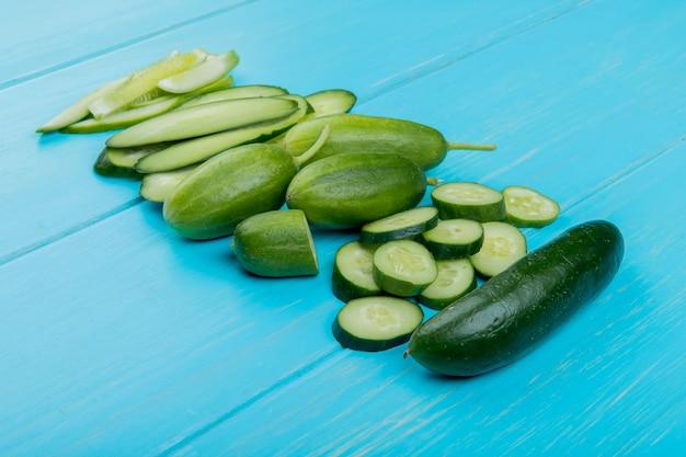 Zijaanzicht van geheel gesneden gesneden komkommers op blauw