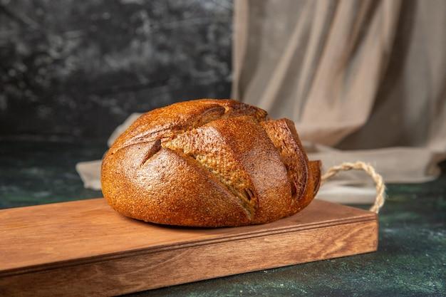 Zijaanzicht van geheel vers zwart brood op bruine houten snijplank op donkere ondergrond