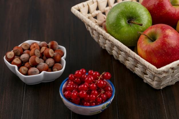 Zijaanzicht van gekleurde appels in een mand met hazelnoten en rode aalbessen in kommen op een houten oppervlak