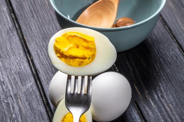 Zijaanzicht van gekookt ei half met vork op houten plattelander