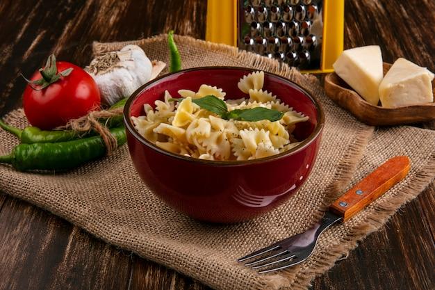 Zijaanzicht van gekookte pasta in een kom met een vork tomaten chili pepers knoflook en kaas op een beige servet