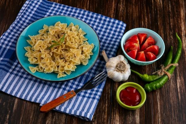 Zijaanzicht van gekookte pasta op een blauw bord op een blauw geruite handdoek met een vork tomaten knoflook en chilipepers op een houten oppervlak
