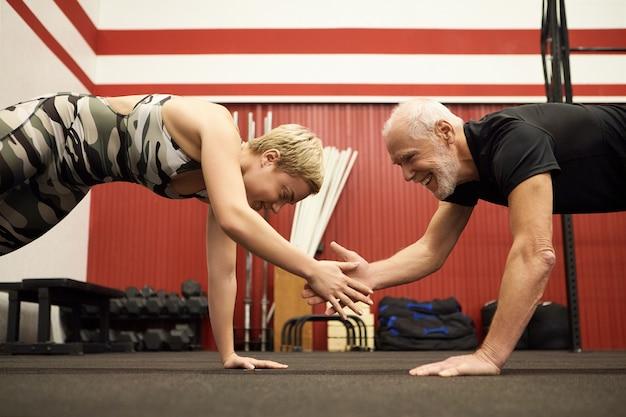 Zijaanzicht van gelukkig bebaarde senior man doet plank in de sportschool met zijn mooie fit vrouwelijke trainer, handen klappen om oefening ingewikkelder te maken. gezonde actieve levensstijl, mensen, leeftijd en fitnessconcept