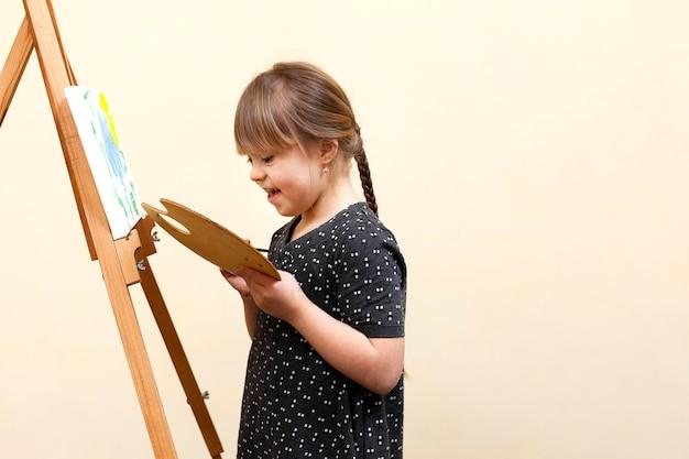 Zijaanzicht van gelukkig meisje met het syndroom van down schilderen