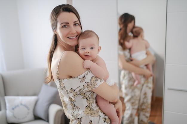 Zijaanzicht van gelukkige blanke moeder met haar liefdevolle glimlachende 6 maanden oude zoon gekleed in luier. op de achtergrond is spiegel.