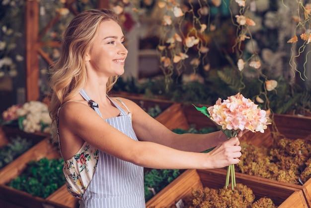 Zijaanzicht van gelukkige glimlachende jonge vrouwelijke bloemist die de hydrangea hortensia aanbiedt