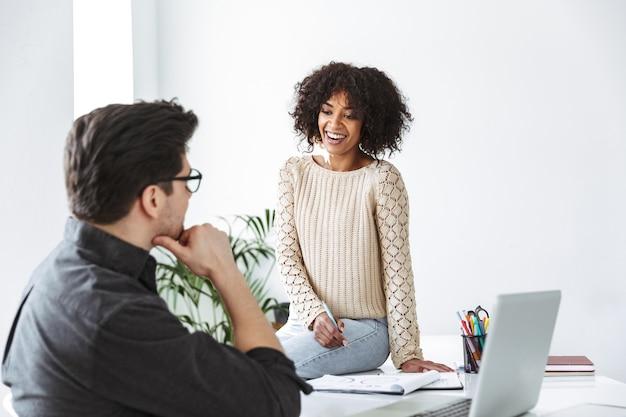 Zijaanzicht van gelukkige jonge collega's die naar elkaar praten en naar elkaar kijken terwijl ze op kantoor zijn