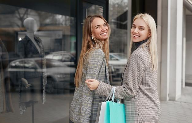 Zijaanzicht van gelukkige jonge vriendinnen in trendy geruite jassen kijken terwijl je in de buurt van showcase van moderne mode winkel, en genieten van tijd samen winkelen