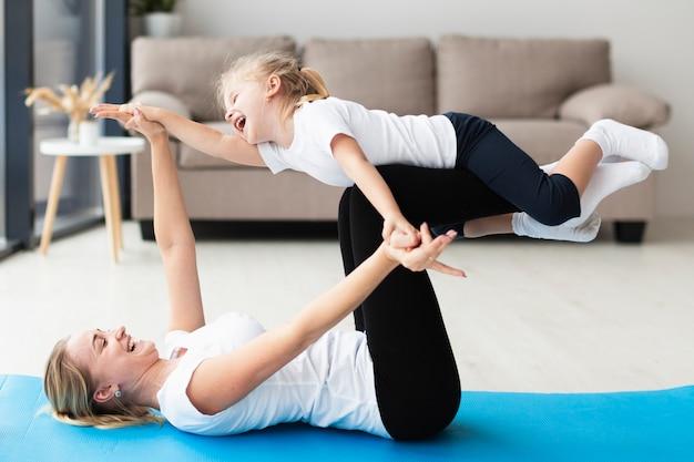 Zijaanzicht van gelukkige moeder en dochter thuis op yogamat