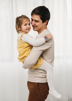 Zijaanzicht van gelukkige vader die zijn dochter houdt