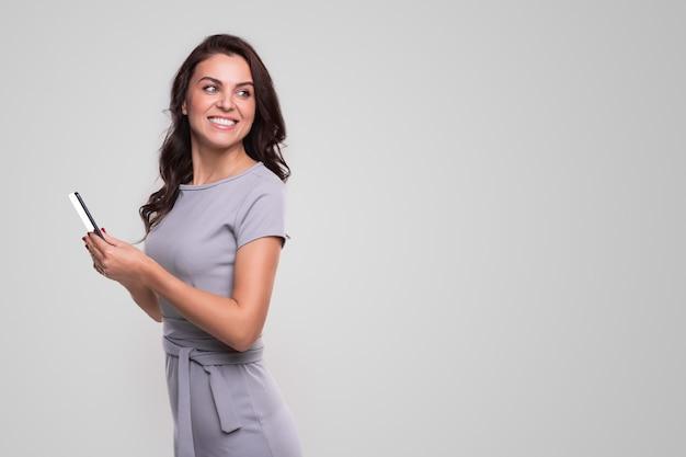 Zijaanzicht van gelukkige volwassen zakenvrouw in elegante jurk wegkijken over schouder tijdens het gebruik van mobiele telefoon