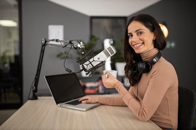 Zijaanzicht van gelukkige vrouw die radio doet