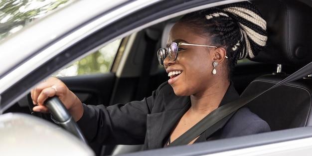 Zijaanzicht van gelukkige vrouw haar eigen auto rijden