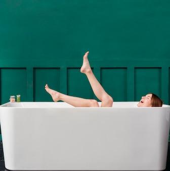 Zijaanzicht van gelukkige vrouw in badkuip