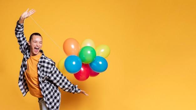 Zijaanzicht van gelukkige vrouw met ballons