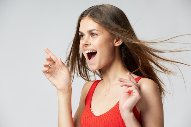 Zijaanzicht van gelukkige vrouw met open mond gebaren met handen op een licht en lachen
