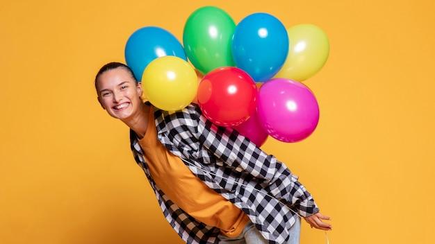 Zijaanzicht van gelukkige vrouw met veelkleurige ballonnen