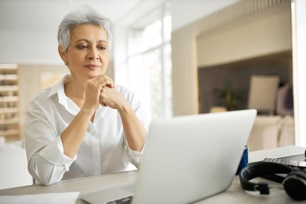 Zijaanzicht van gelukkige zakenvrouw van middelbare leeftijd met kort grijs haar bezig met laptop in haar stijlvolle kantoor met handen op toetsenbord, brief typen, goed nieuws delen