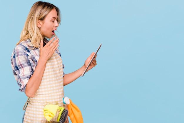 Zijaanzicht van geschokte jonge vrouw met mond open holdings digitale tablet vooraan blauwe achtergrond