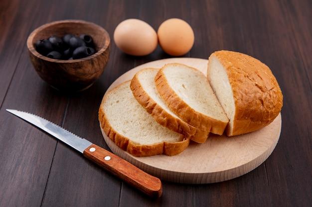 Zijaanzicht van gesneden brood op snijplank en mes met eieren en kom met zwarte olijven op hout