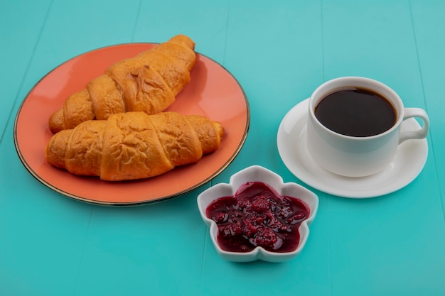 Zijaanzicht van gesneden croissants en frambozenjam met kopje thee op blauwe achtergrond
