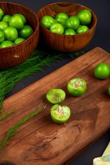 Zijaanzicht van gesneden groene pruimen besprenkeld met gedroogde pepermunt op een houten snijplank en houten kommen gevuld met groene pruimen op zwarte tafel