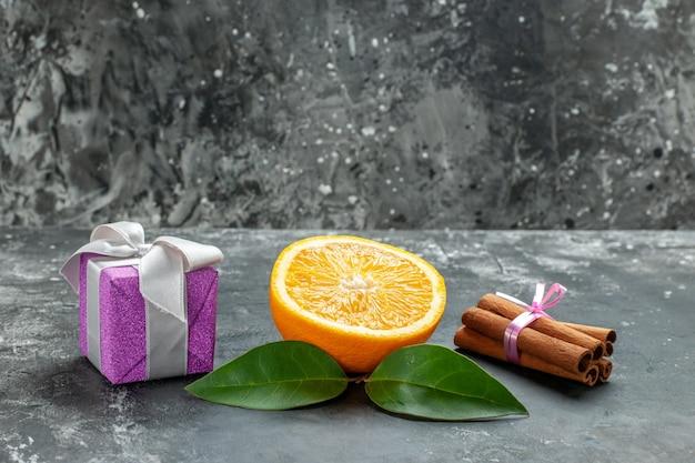 Zijaanzicht van gesneden verse sinaasappel in de buurt van een geschenk en kaneellimoenen op donkere achtergrond