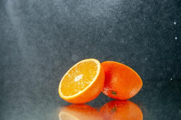 Zijaanzicht van gesneden verse sinaasappelen die naast elkaar staan op licht op zwarte achtergrond met vrije ruimte
