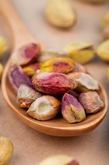 Zijaanzicht van gezouten geroosterde pistachenoten op houten lepel
