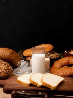 Zijaanzicht van glas met melk en gesneden wit brood op snijplank met mes en verschillende soorten brood op zwarte achtergrond met kopie ruimte