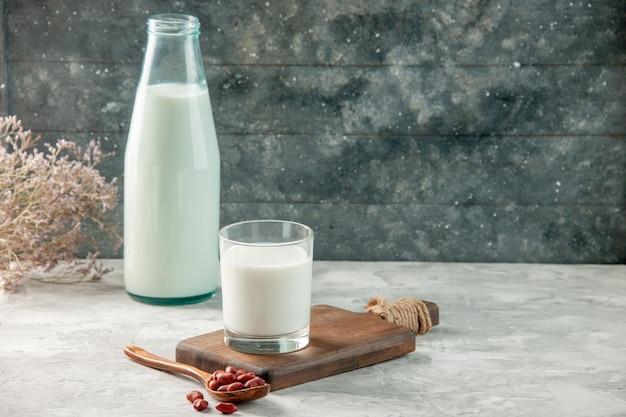Zijaanzicht van glazen beker op houten snijplank en fles gevuld met melk en pinda's op grijze tafel
