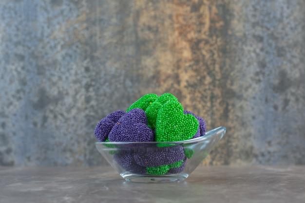 Zijaanzicht van glazen kom vol kleurrijke snoepjes.