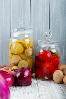 Zijaanzicht van glazen potten met zure tomaten en uien aardappelen op houten oppervlak en achtergrond met kopie ruimte