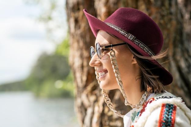 Zijaanzicht van glimlachend peinzend meisje in kastanjebruine hoed en oogglazen met ketting die meer bekijken