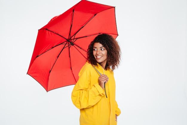 Zijaanzicht van glimlachende afrikaanse vrouw in regenjas het stellen