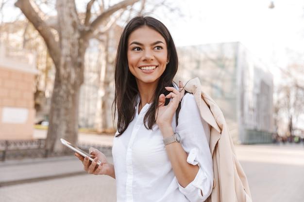 Zijaanzicht van glimlachende donkerbruine vrouw in het jasje van de overhemdsholding