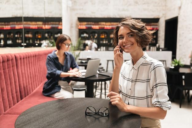 Zijaanzicht van glimlachende krullende vrouw praten door de telefoon