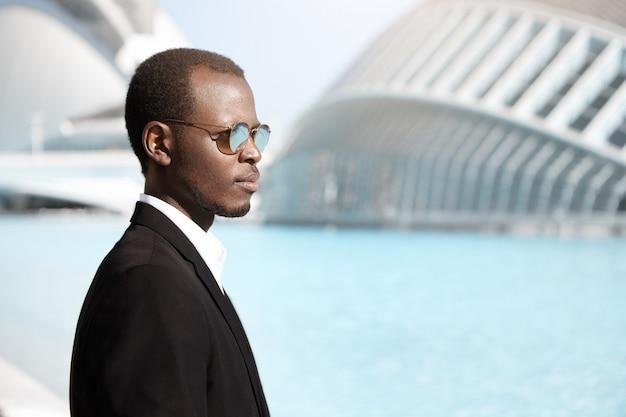 Zijaanzicht van glimlachende stijlvolle bankier met een donkere huidskleur, gekleed in een zwart pak en een ronde zonnebril, lopend naar kantoor in een stedelijke omgeving, met een zelfverzekerde en vastberaden blik, denkend aan een aanstaande vergadering
