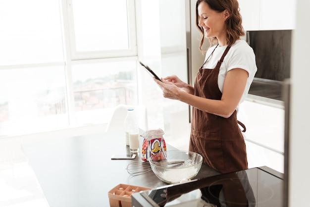 Zijaanzicht van glimlachende toevallige vrouw gebruikend tabletcomputer en kokend op keuken