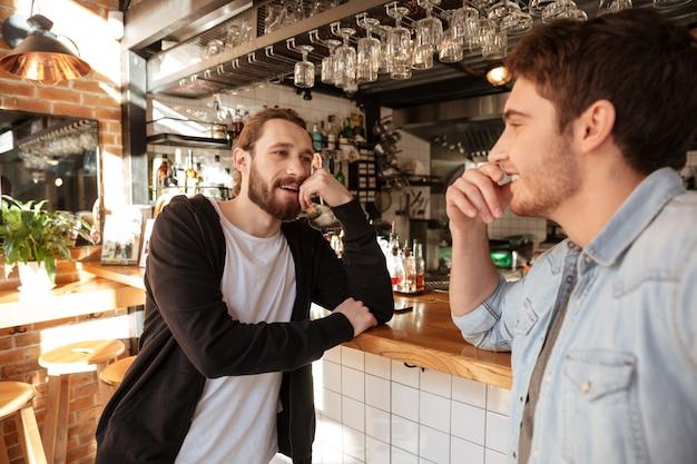 Zijaanzicht van glimlachende vrienden staan in de buurt van de bar