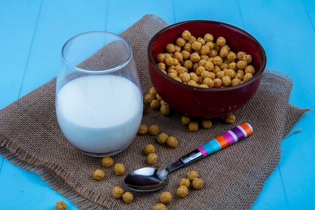Zijaanzicht van granen in kom en glas melk met lepel op zak en blauwe achtergrond